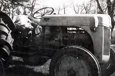 John Thompson and sister Judy riding their Dad's tractor